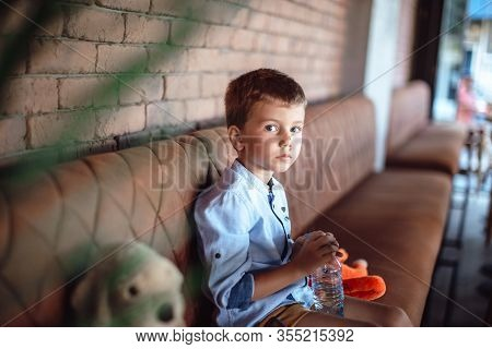Cute, Little Blonde Boy Sitting Alone At The Table With His Teddy Bear. Looking Confused, Worried. H
