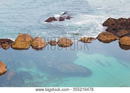 Group Of Natural Rock Formations In Low Tide Water In Monterey Bay, Monterey, California, Usa