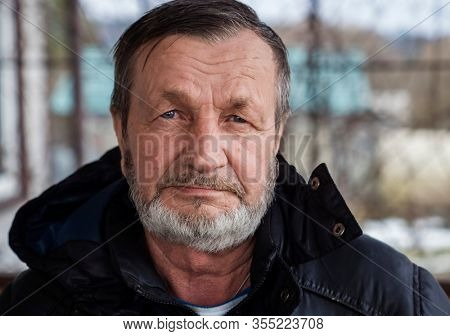 Bearded elderly country man outdoors in winter, real people