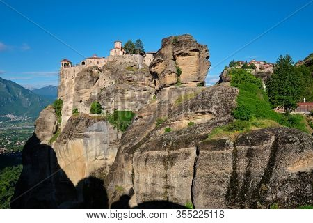 Monastery of Varlaam and Monastery of Great Meteoron in famous greek tourist destination Meteora in Greece on sunrise with scenic scenery landscape