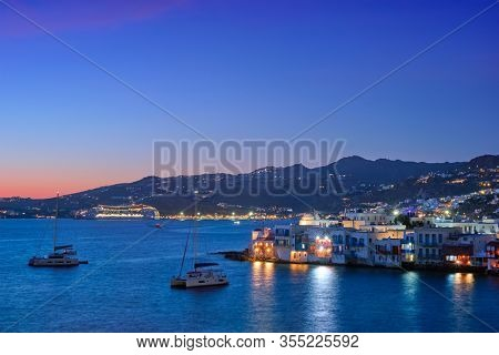Sunset in Mykonos island, Greece with yachts in the harbor and colorful waterfront houses of Little Venice romantic spot on sunset and cruise ship illuminated in night. Mykonos townd, Greece