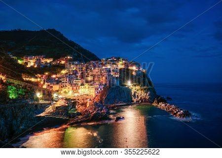 Manarola village popular european italian tourist destination in Cinque Terre National Park UNESCO World Heritage Site, Liguria, Italy illuminated in the evening