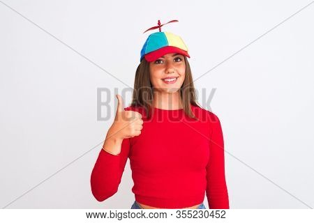 Young beautiful girl wearing fanny cap with propeller standing over isolated white background doing happy thumbs up gesture with hand. Approving expression looking at the camera with showing success.
