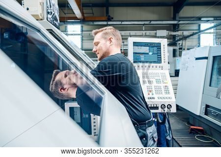 Experienced worker resetting a cnc lathe machine in manufacturing factory
