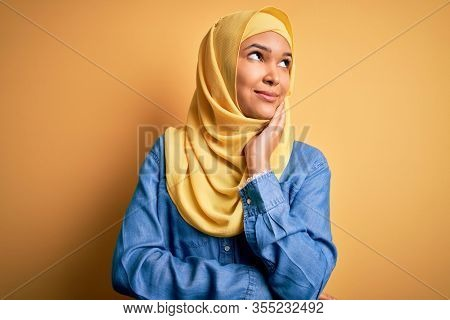 Young beautiful woman with curly hair wearing arab traditional hijab over yellow background with hand on chin thinking about question, pensive expression. Smiling and thoughtful face. Doubt concept.
