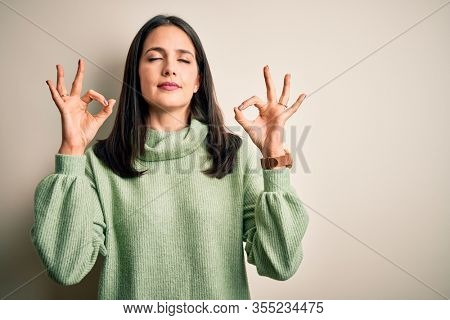 Young brunette woman with blue eyes wearing turtleneck sweater over white background relax and smiling with eyes closed doing meditation gesture with fingers. Yoga concept.