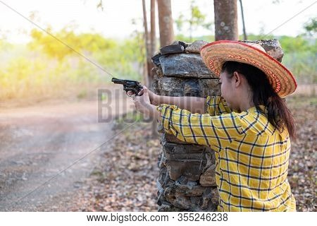 Portrait The Farmer Asea Woman Wearing A Hat At The Shooting Shot From Old Revolver Gun In The Farm,