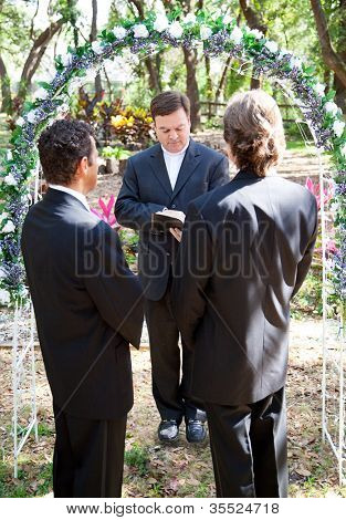 Gay couple being married by their minister outdoors under a floral archway.