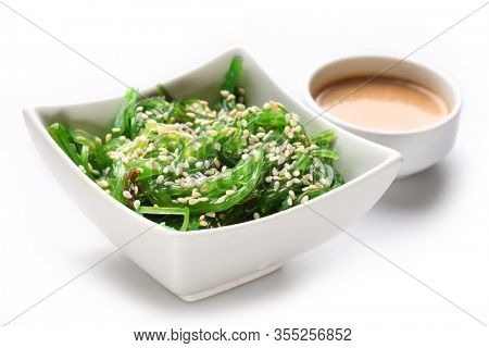 Japanese hiyashi wakame chuka salad with white sesame seeds and peanut sauce in a bowl on a white background.
