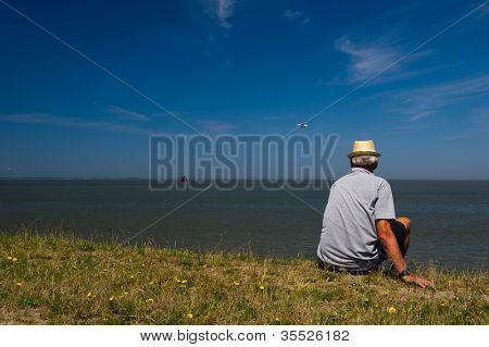 Man sitting at the dike from Dutch wadden sea