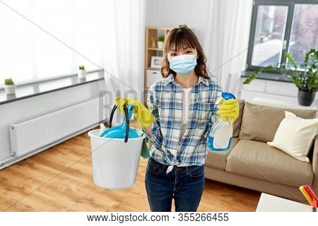 health and hygiene concept - smiling asian woman wearing protective medical mask for protection from virus holding bucket of cleaning stuff and detergent at home