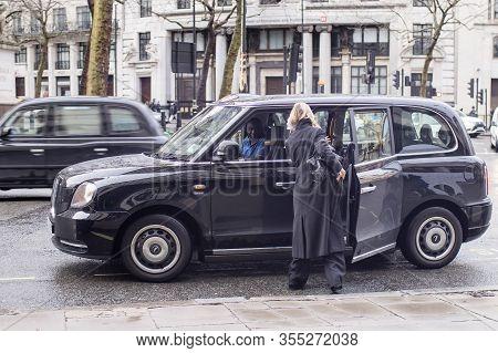 London, Uk- Febryary 15 2020: Fashionable People On The Street . Street Style. Girls In Raincoats Of