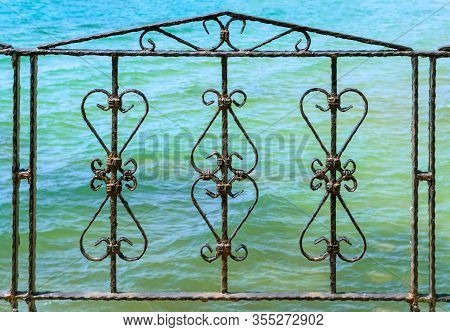 Decorative Wrought Iron Metal Fence. Front View. Metal Fence. Blue Sea Water In The Background. An O