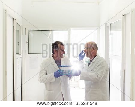 Two Colleagues Communicating And Laughing While Holding Samples In Test Tubes In Laboratory