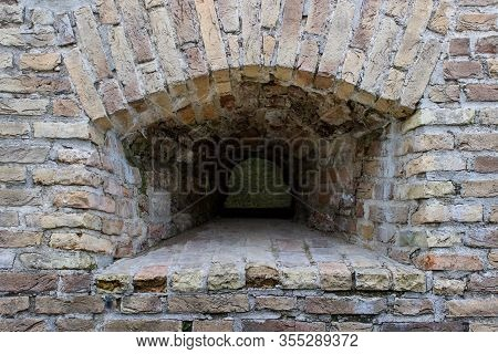 Small Window Embrasure In The Old Ancient Historical Brick Wall.