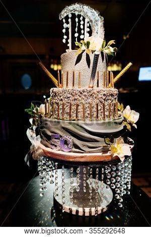 Tiered Birthday Cake With Beads And Candles In The Dark