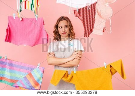 Image of displeased sad woman housewife isolated over pink wall background dry clothes on rope.