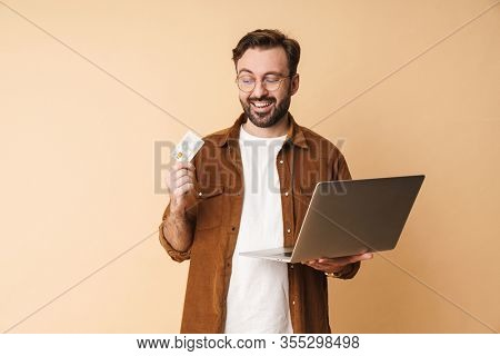 Image of a positive young unshaved man isolated over beige wall background using laptop computer holding credit card.