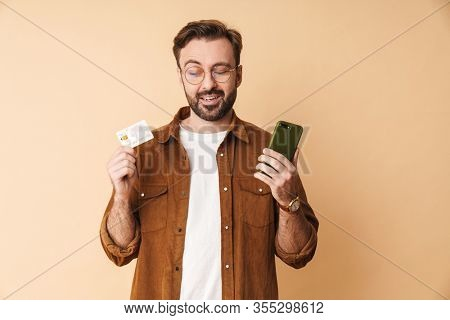 Image of a concentrated serious young unshaved man isolated over beige wall background holding credit card using mobile phone.