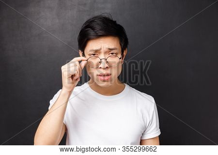 Close-up Portrait Of Arrogant Skeptical Asian Man In White T-shirt, Squinting With Doubt Take-off Gl