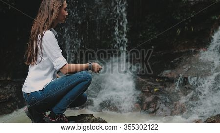 Girl Hiker Crouch near Tropical Forest Waterfall. Caucasian Woman Explorer Squat on Stone. Splashing Mountain Stream. Wild Babbling Brook on Cascade Rocks.
