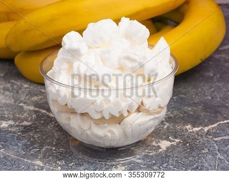 Dessert: Whipped Cream With Banana In A Cream Bowl On A Gray Background
