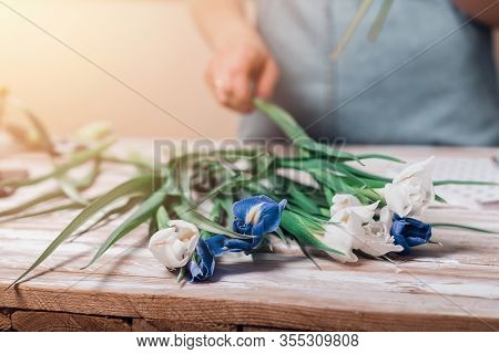 Hands Of Young Woman Florist Working With Fresh Flowers Making Bouquet Of Fleur-de-lises On Table.