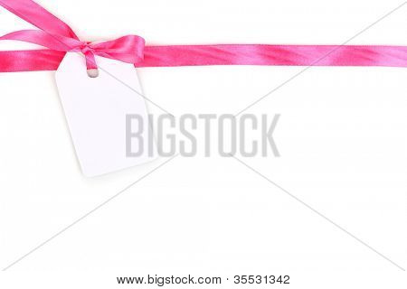 Blank gift tag with pink satin bow and ribbon isolated on white
