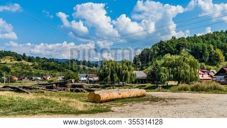 Logs With Houses, Forest And Puffy Clouds In The Background On A Sunny Day