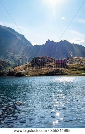 Sun Casting Rays On A Mountain Lake With Mountain Chalet And Mountain  In The Background And Puffy C