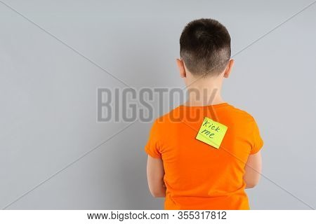 Preteen Boy With Kick Me Sticker On Back Against Light Grey Background. April Fool's Day
