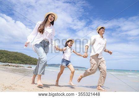 Asian Family Having Fun Running On A Sandy Beach In Pattaya, Thailand