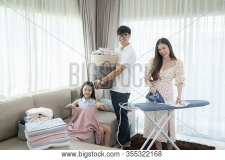 Beautiful Young Woman And A Man And Child Girl Little Helper Are Having Fun And Smiling While Ironin