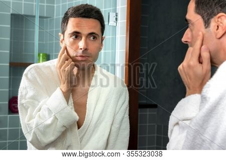 Close Up Portrait Of Middle Aged Man In Bathrobe Reviewing Wrinkles And Sagging Skin In Bathroom Mir