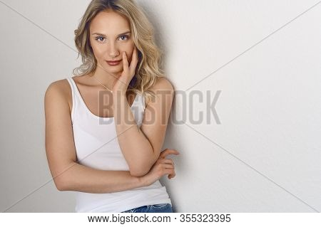 Attractive Blond Woman With Tousled Hair Wearing A Summer Top And Jeans Giving The Camera A Serious