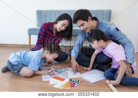 Young Happy Smiling Couple And Family Choosing Colors For Painting Their Home, This Image Can Use Fo