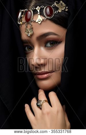 A Conceptual Middle Eastern Portrait Of A Woman's Face Decorated With Oriental-style Jewelry On A Bl