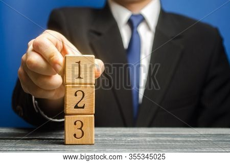 Businessman Puts Wooden Blocks With The Number 1 2 3. Task List. Alternate Items And Conditions For