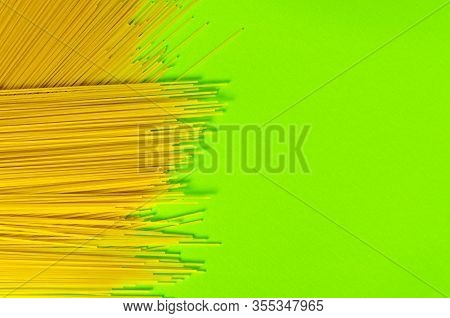 Yellow Long Spaghetti On A Light Green Background. Yellow Italian Pasta. Long Spaghetti. Raw Spaghet