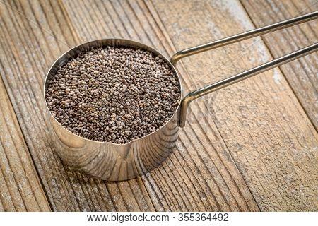 chia seeds in metal measuring scoop against grunge wood background, healthy superfood concept