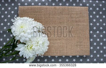 Rustic Brown Burlap Cloth Isolated On Gray Background.white Spray Chrysanthemums On Burlap Backgroun
