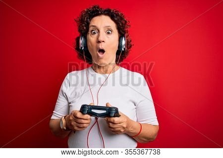 Middle age curly hair gamer woman playing video game using joystick and headphones scared in shock with a surprise face, afraid and excited with fear expression