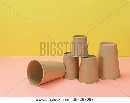 Eco-friendly Paper Cups In Pink And Yellow Background. Disposable Ware.