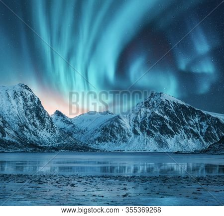 Northern Lights Over The Snowy Mountains, Coast Of The Lake And Reflection In Water. Aurora Borealis