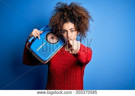 Young beautiful woman with curly hair and piercing listening to music using vintage radio pointing with finger to the camera and to you, hand sign, positive and confident gesture from the front