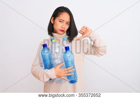Young beautiful chinese woman recycling plastic bottles over isolated white background with angry face, negative sign showing dislike with thumbs down, rejection concept