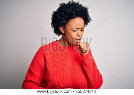 Young beautiful African American afro woman with curly hair wearing red casual sweater feeling unwell and coughing as symptom for cold or bronchitis. Health care concept.