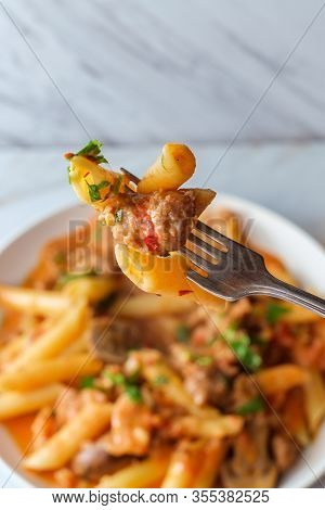 Italian Penne Pasta In Creamy Vodka Tomato Sauce With Crumbled Sausage And Mushrooms On Marble Kitch