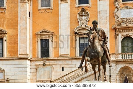 Rome Italy. Bronze statue of Roman Emperor Marcus Aurelius on steed at Capitol square among vintage buildings with ancient architecture.