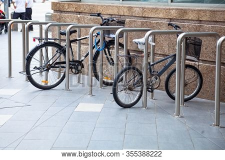 Bicycle Top Tubes Are Securely Chained, By Chain Links And Locks, To The Metal Bike Racks. Outdoor A